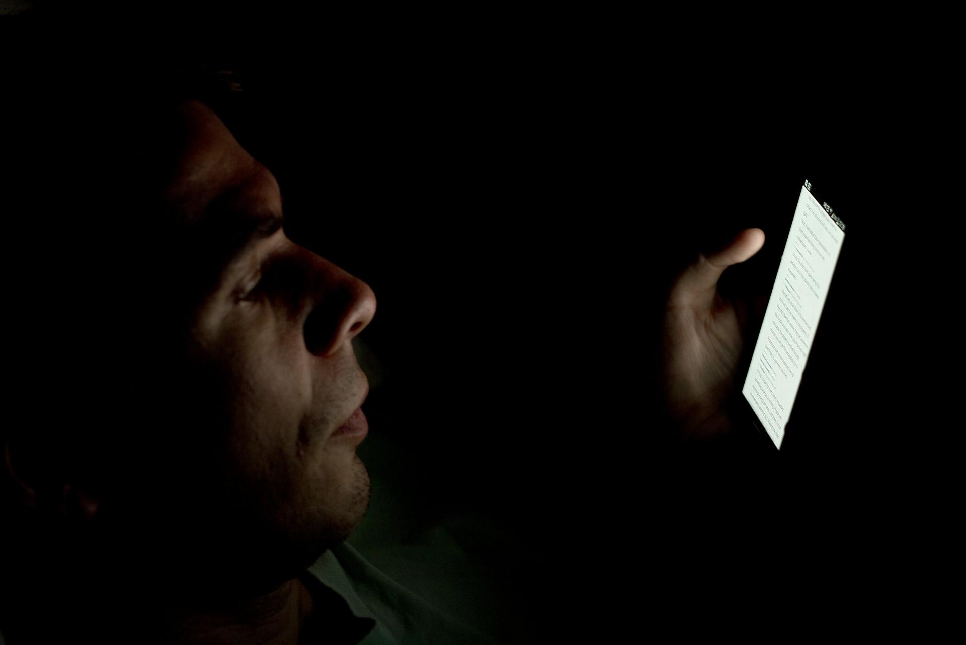 man looking at smartphone in the dark