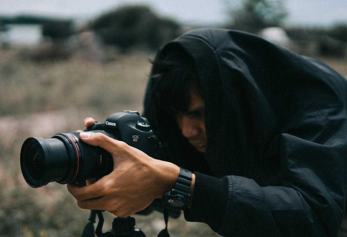 A photographer sights his camera with his dominant eye.