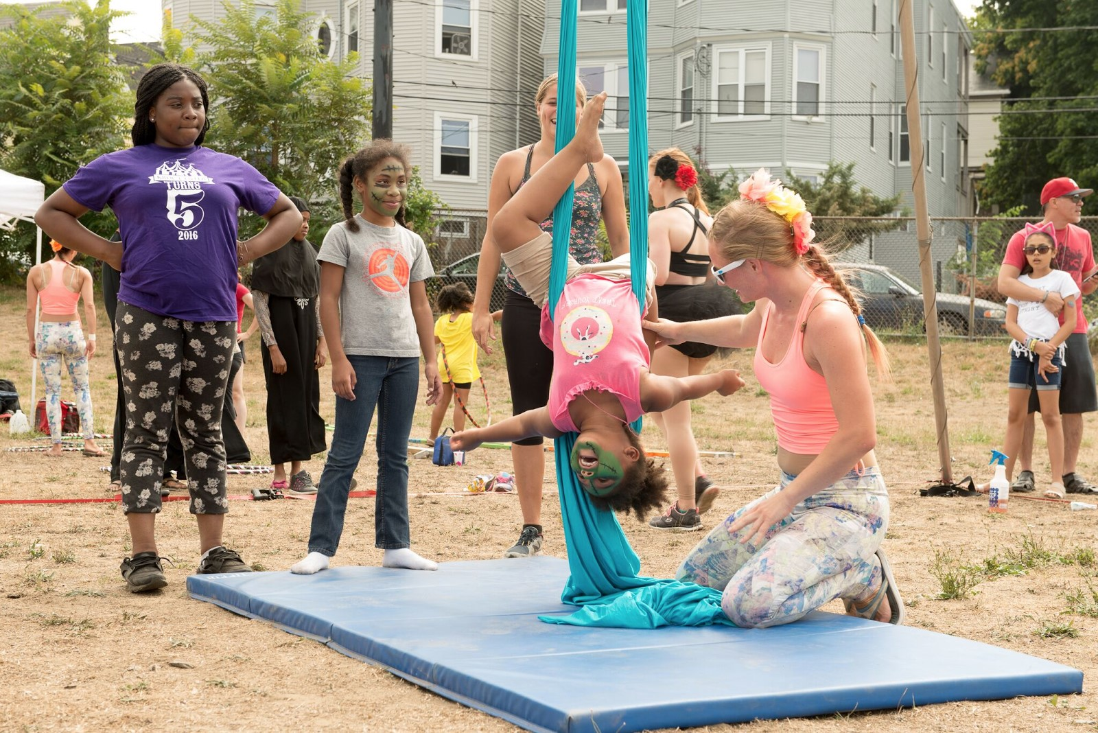 A Circus Up performer teaches a little girl at DSNI's 28th Annual Multicultural Festival. Image shows a little girl, with her face painted, hanging upside down from blue fabric, being helped by a performer at Mary Hannon Park in Dorchester. Photography by Mark Fusco.