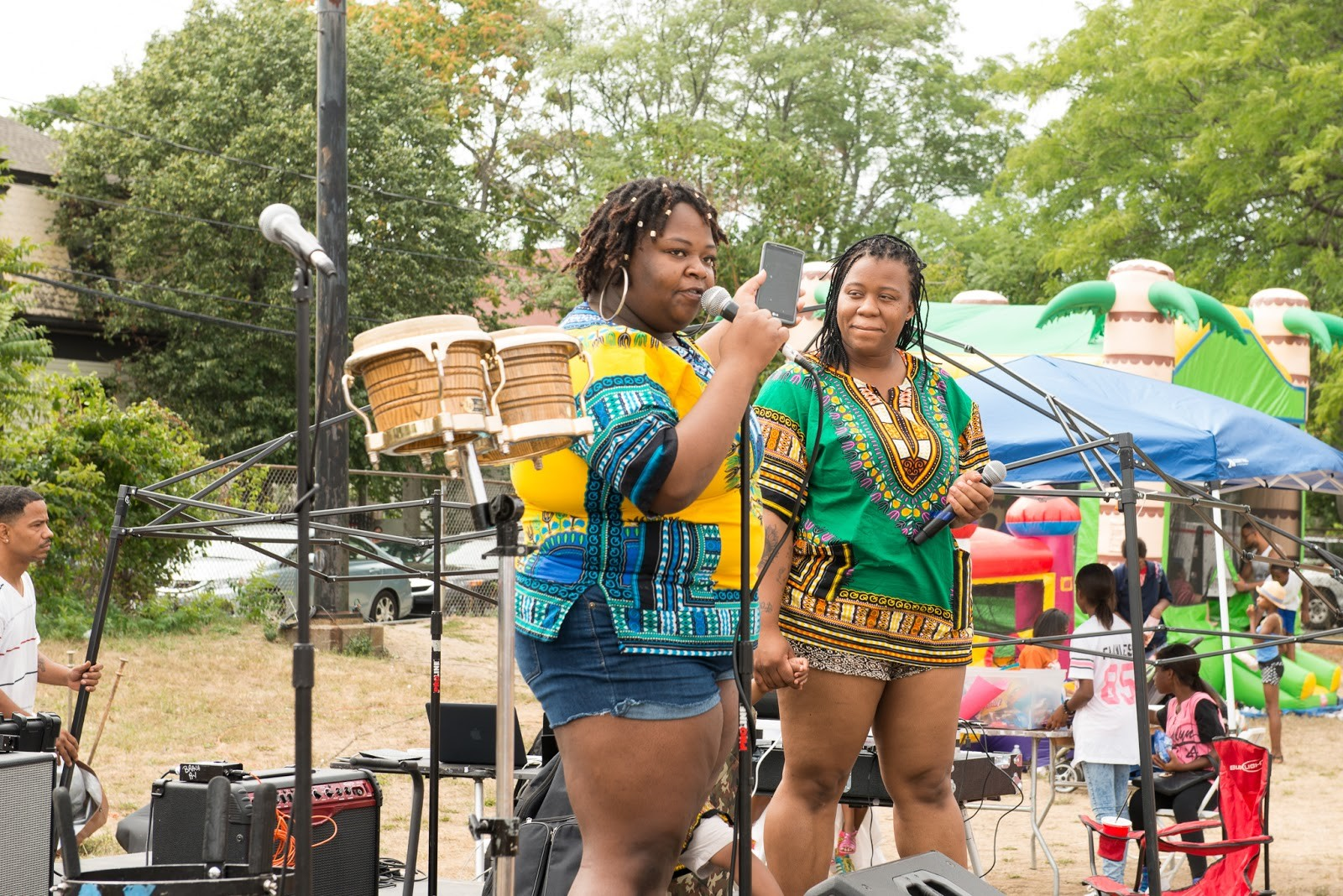 Jaimorry Carter and Ava Mootrey perform at DSNI's 28th Annual Multicultural Festival. Image shows Jaimorry, in a yellow and blue tunic, speaking into a microphone and Ava, in a green and orange tunic, holding a microphone, at Mary Hannon Park in Dorchester. Photography by Mark Fusco.