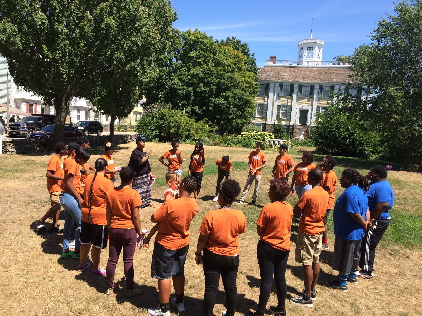 Summer Youth Organizer prepare for DSNI's 28th Annual Multicultural Festival. Image shows young people in orange shirts standing in a circle in front of the Shirley Eustis House in Roxbury. Photography by Ros Everdell.