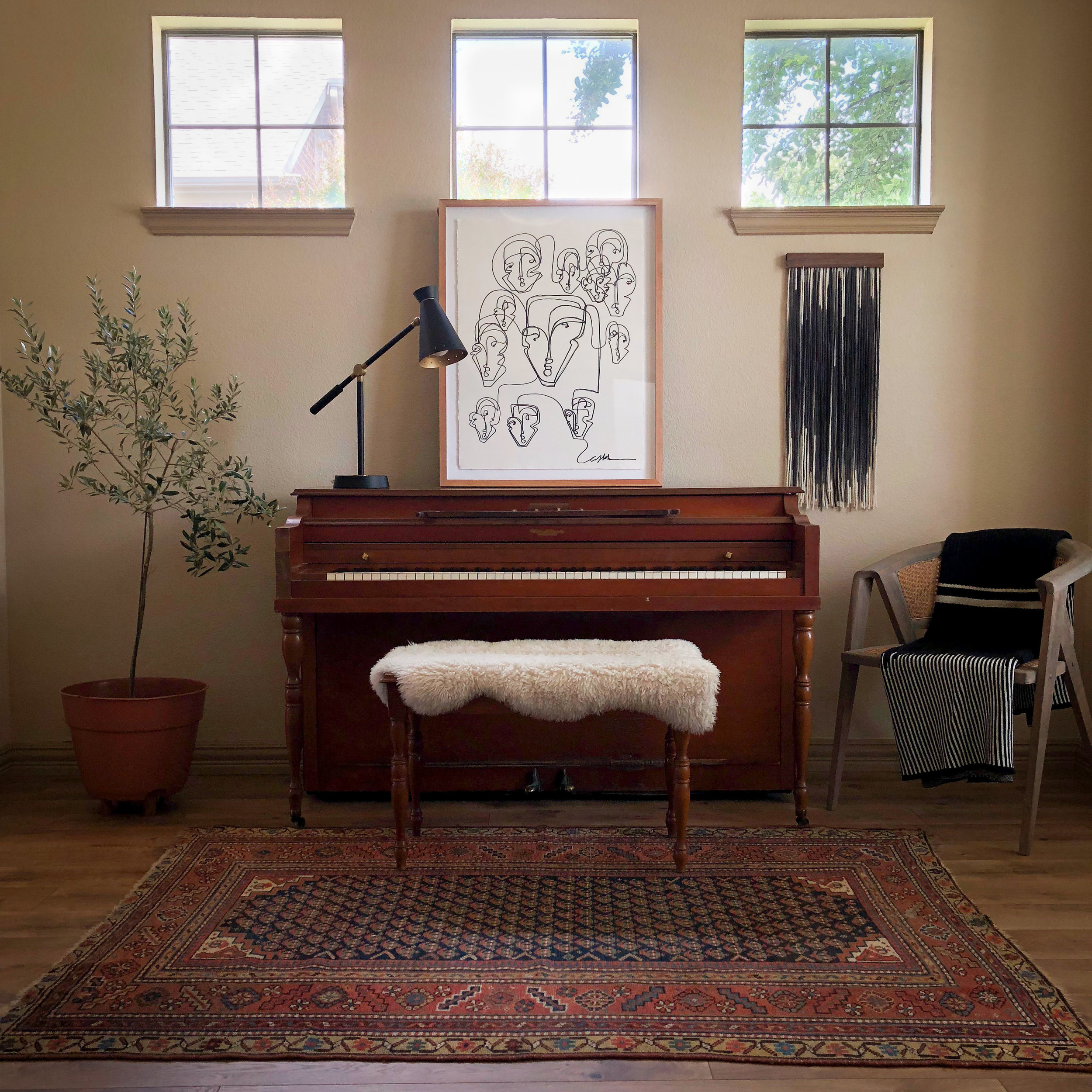 Mini Tapestry paired with framed art by Carly Kuhn of @thecartorialist in Lauren's family piano room. Vintage upright piano and bench found on Craigslist. Vintage rug from Jean Palmer Home. Chair with Lauren Williams + Ditto House tapestry-inspired cotton knit throw available online: https://www.laurenwilliamsart.com/store