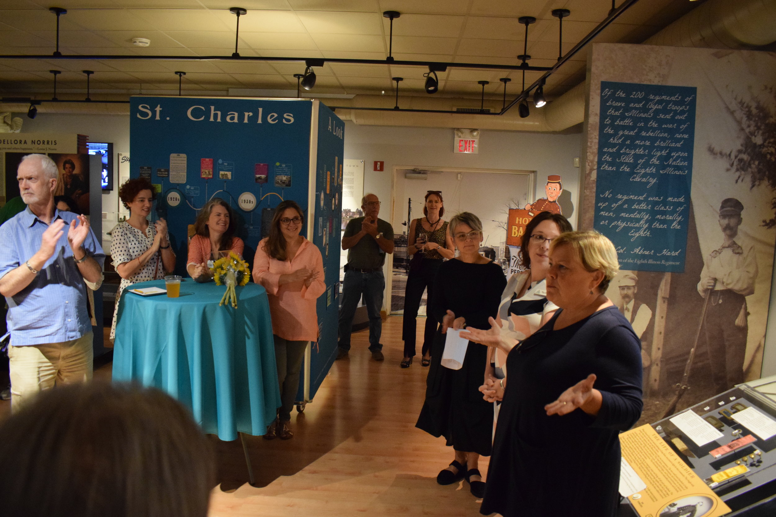 Director of the St. Charles Arts Council Kathryn Hill (far right), Director of the St. Charles History Museum Alison Costanzo, (second from right), and Artist Rita Grednze (third from right) unveil  Synapses 4  at the special opening reception on Sept. 5