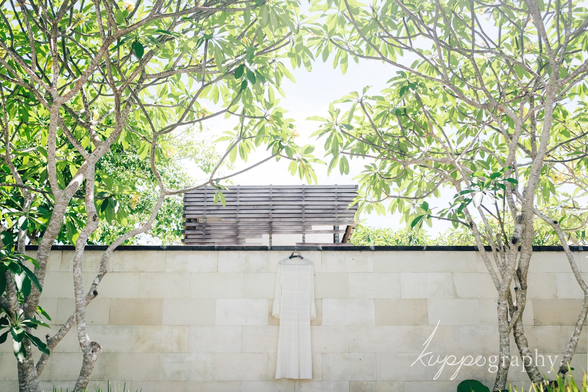 プライベートヴィラ内の壁にウェディングドレスをかけて撮影
