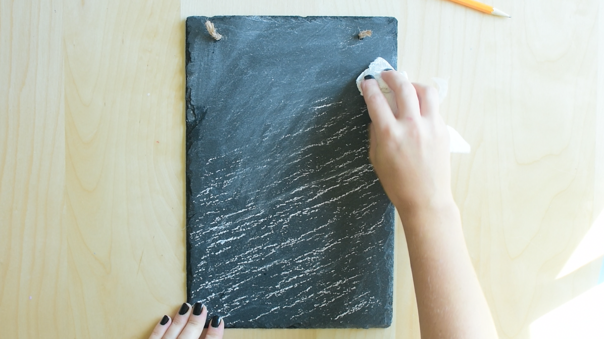 Prep chalkboard surface by spreading chalk all over it