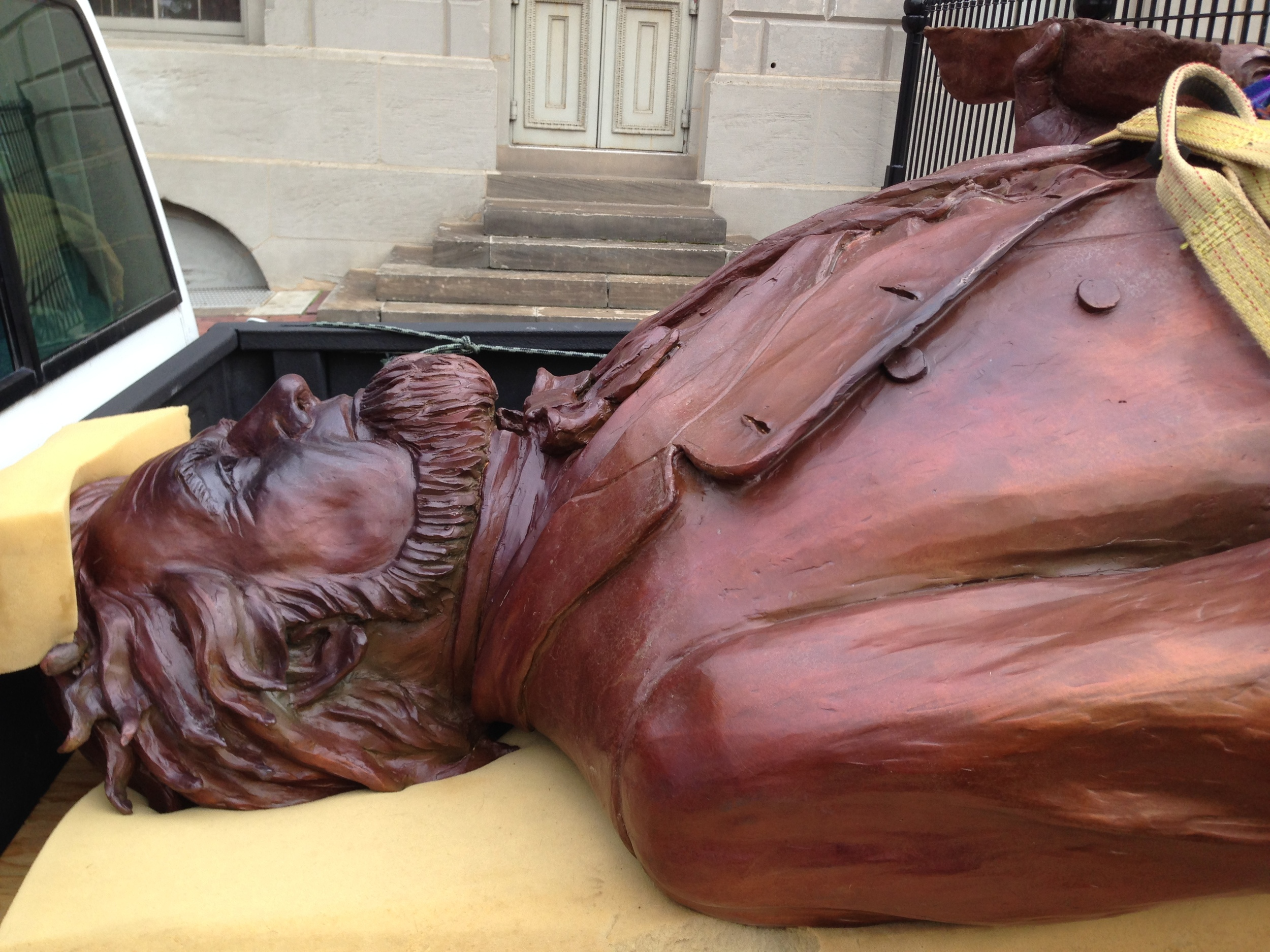 The bronze statue of Francis Pierpont lay in the back of the artist's pickup Friday until workers secured it to the pedestal outside West Virginia Independence Hall.