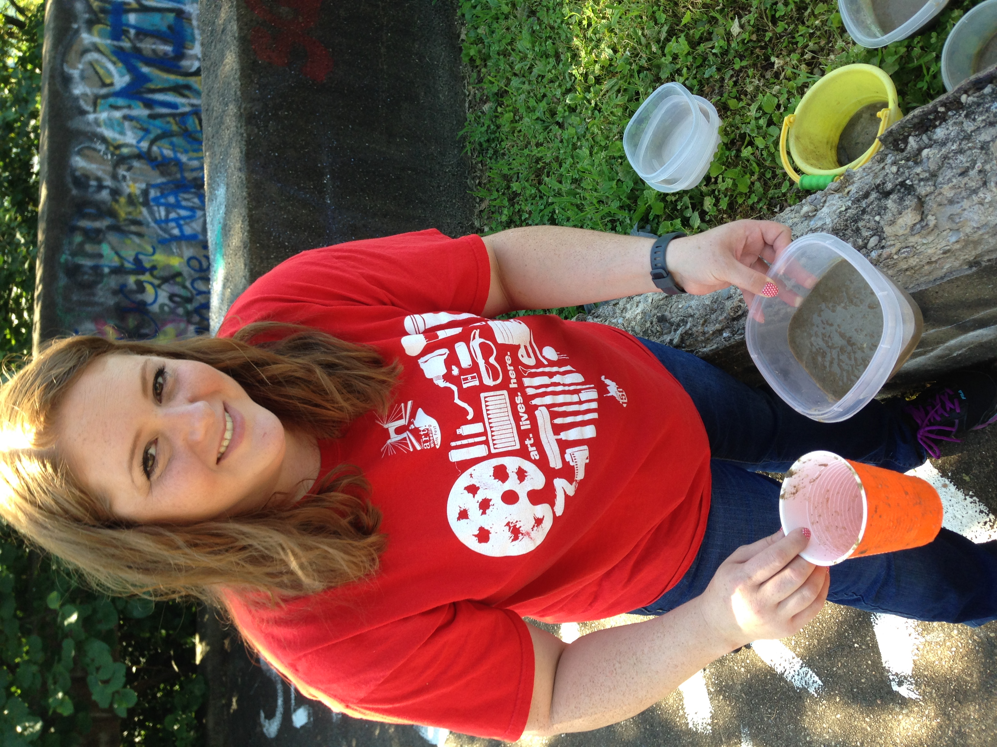 Erika Donaghy shows off the slurry solution as she pours it in to plastic containers and passes them out to volunteers to go painting.