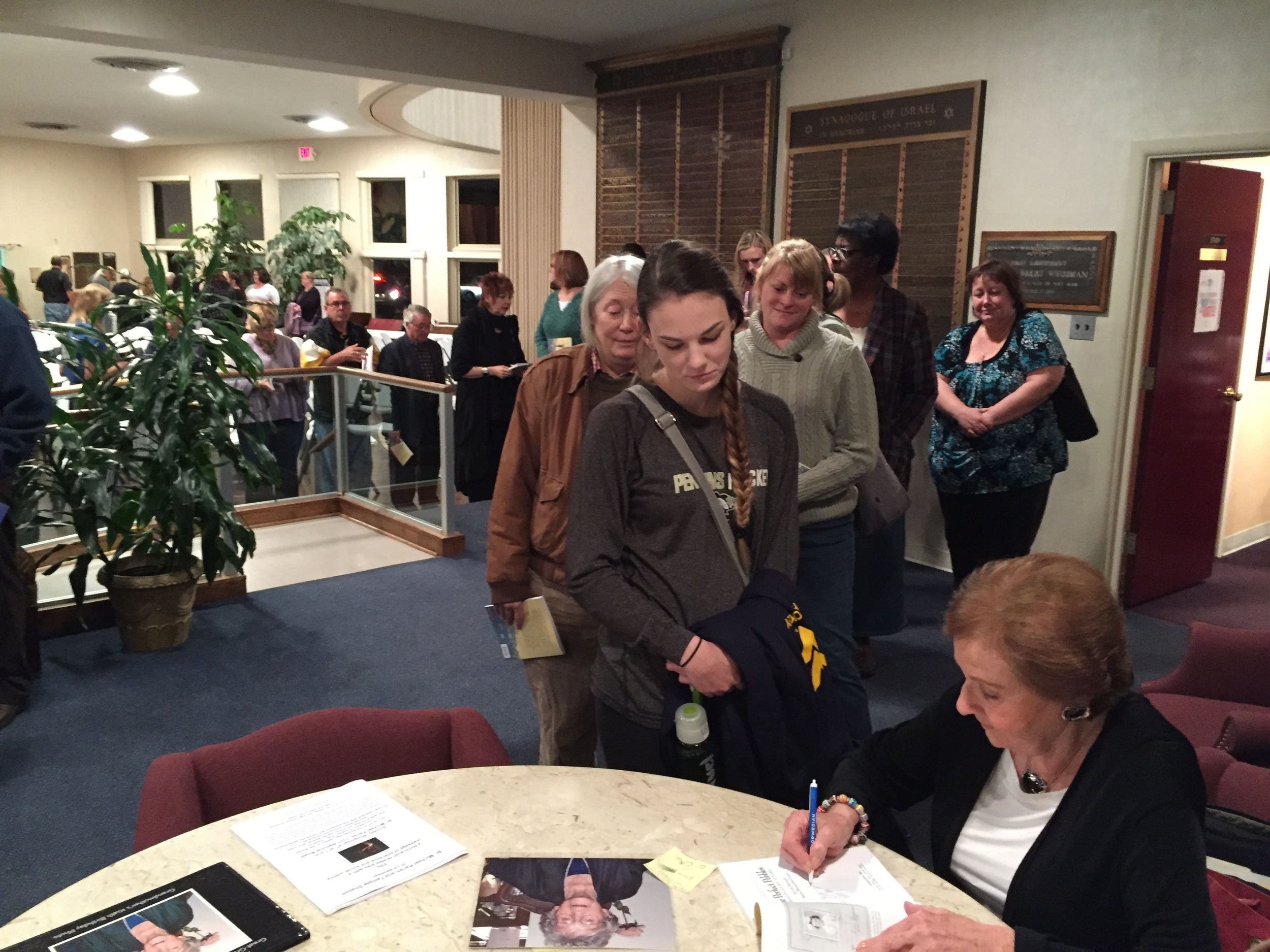 Marion Blumenthal Lazan autographs copies of her memoir, Four Perfect Pebbles, following her lecture Sunday at Temple Shalom.
