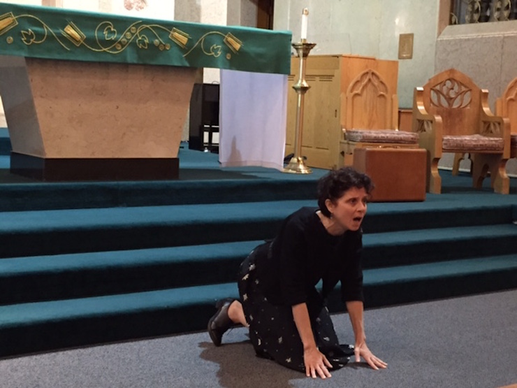 Susan Stein, who portrays Etty in the one-woman show of the same title, drops to her knees and chants a Hebrew psalm during her performance Sunday at St. Michael's Church.