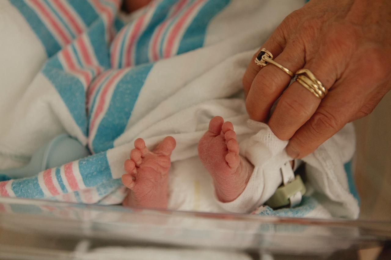 生まれたてのしわくちゃな足と、年を刻んだ優しい義母の手。