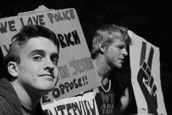 "8 October 2011 Two protesters welcome passersby to ask them questions about the meaning and goals of the Occupy Wall Street movement. ""We love police. We love rich people. It's the system we oppose!!"" says their sign."