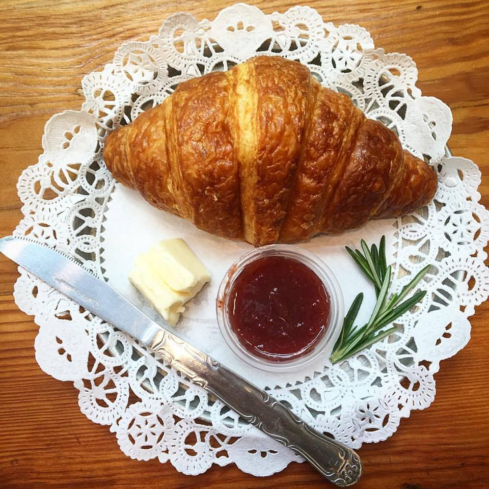 Fresh-baked croissant with strawberry jam and butter for brunch snackin'