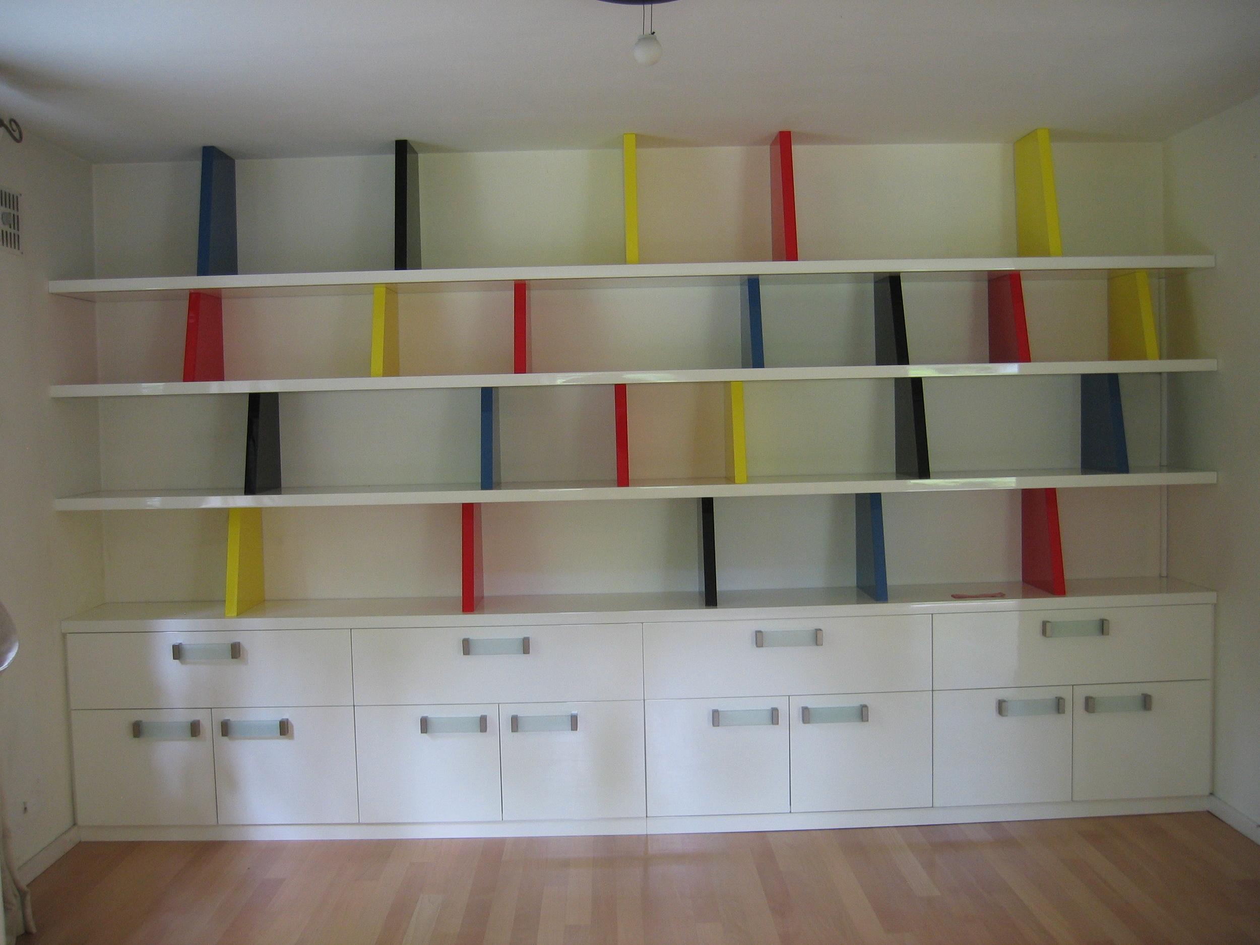 boekenwand van hoogglans gespoten mdf, met opbergruimte in lades en achter deurtjes