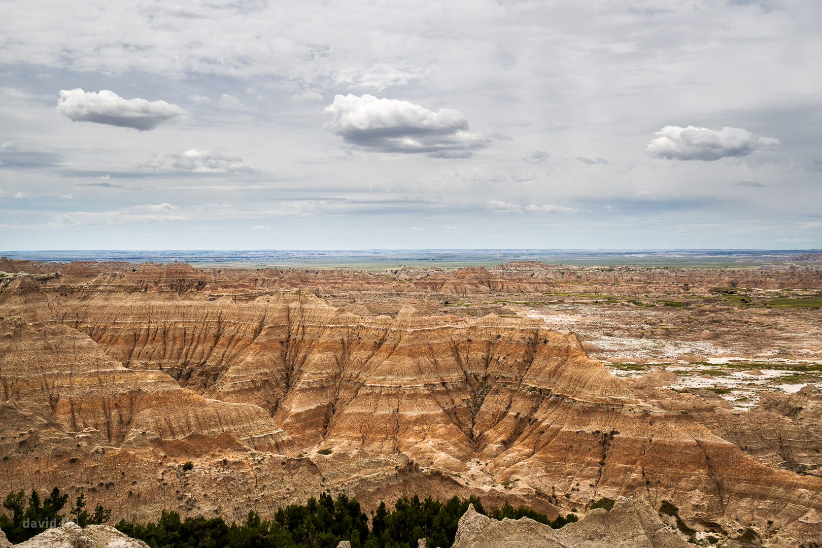 The eroded ridges and spires unveil the many different layers of rock and soil usually concealed beneath the grasslands of Badlands.