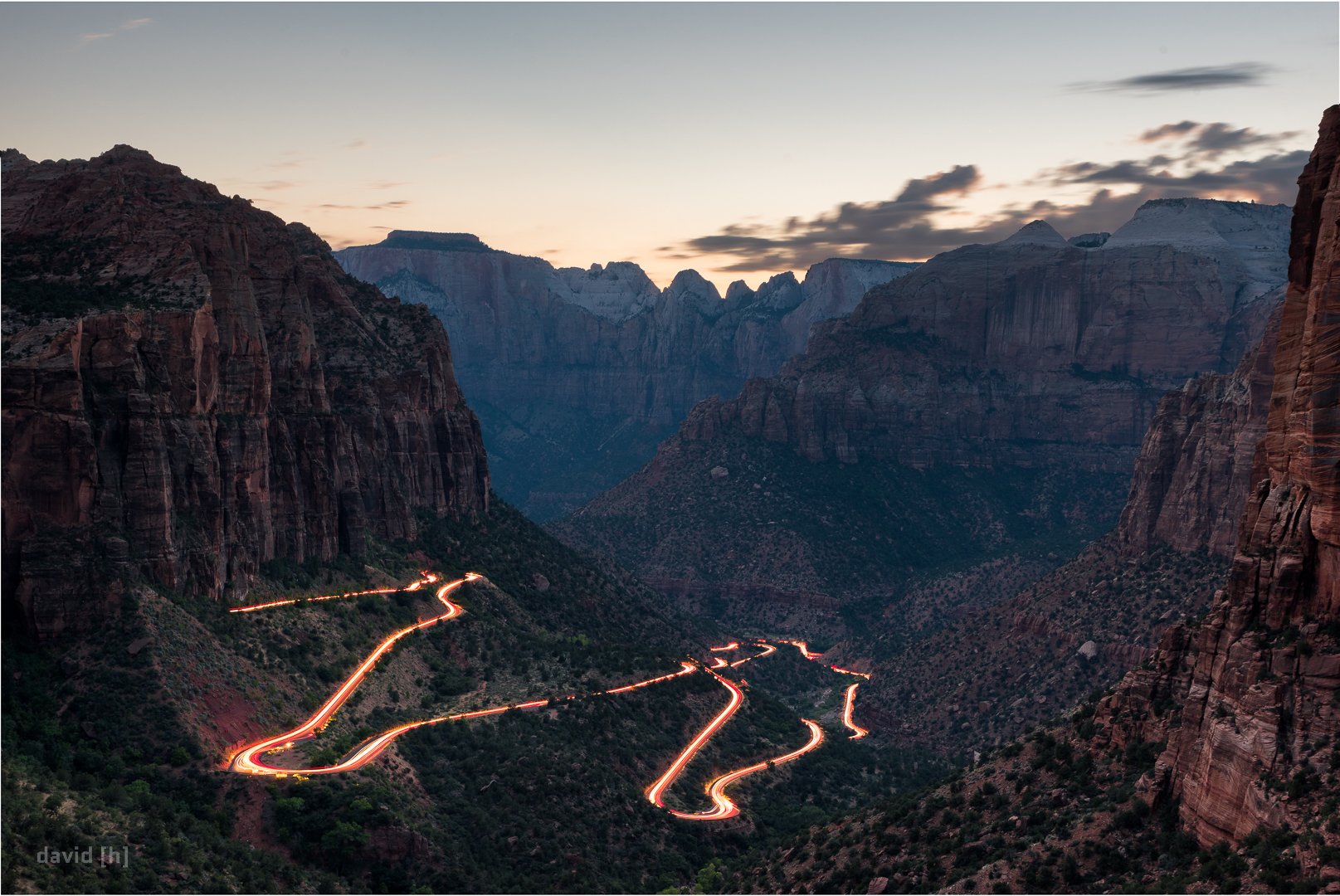 Cars snaking their way up to Canyon Overlook after sunset.