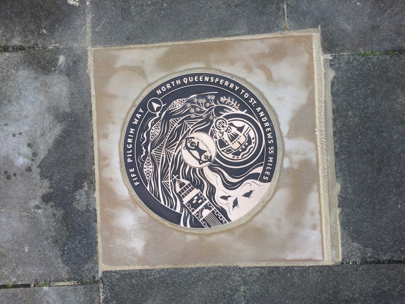 One of the bronze floor discs installed into the pavement