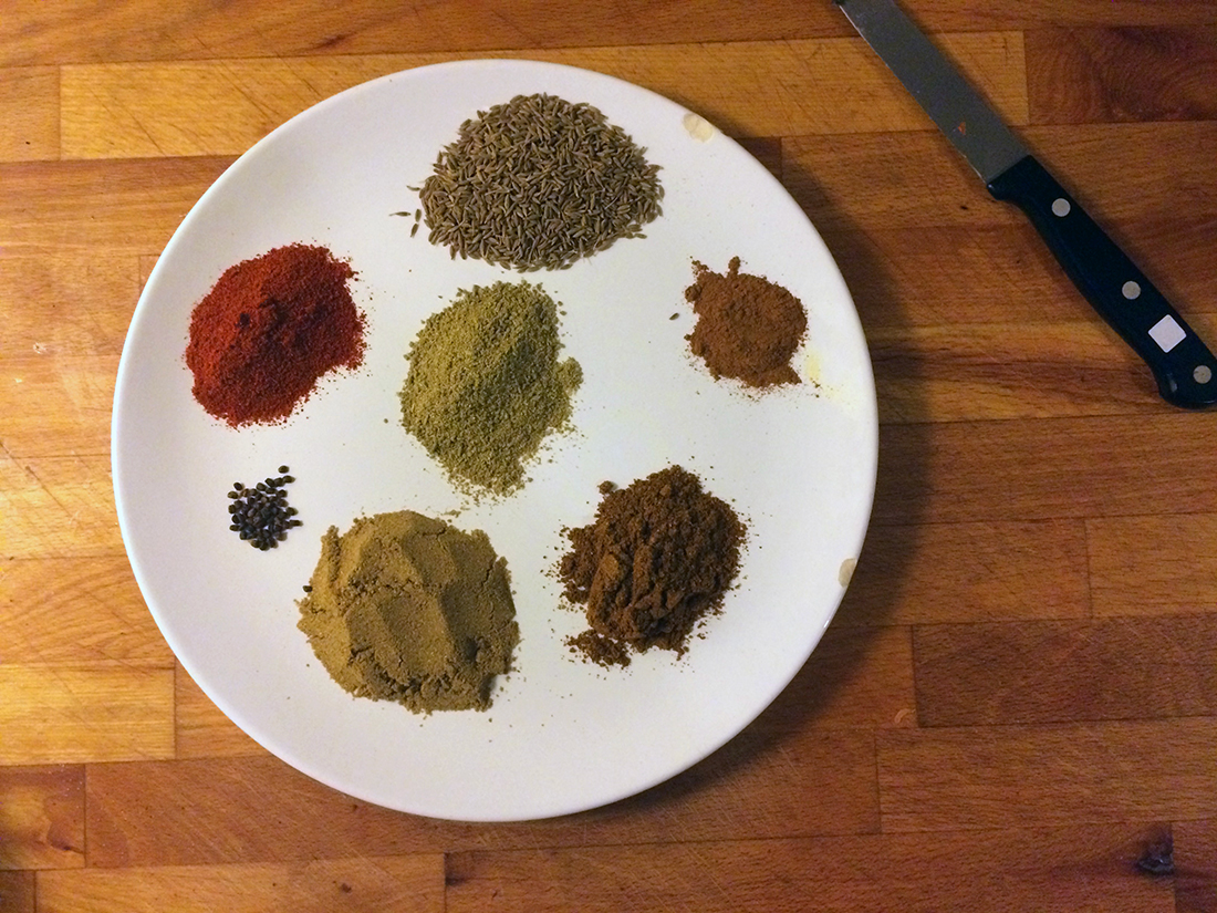 The spices. Starting from left Chili powder (red one), Cumin seeds, Cinnamon powder, Garam Masala, Corriander powder, Cardamom seeds and Fennel powder (in the middle.)
