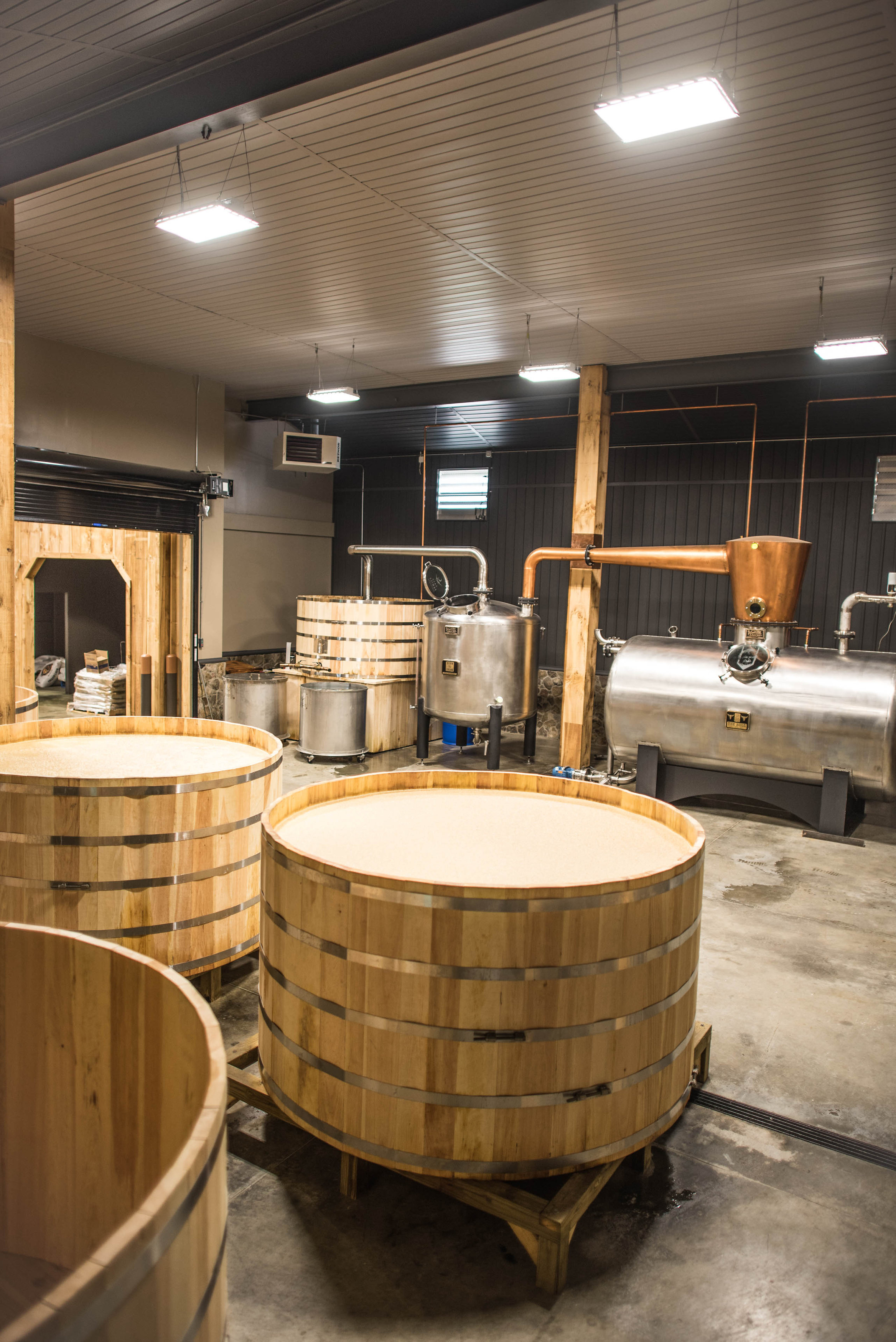"""Call Family Distillers stillhouse. 1,000 gallon open fermentation barrels in the front. """"The Bull"""" a 2,100 gallon direct steam injection still in the background."""