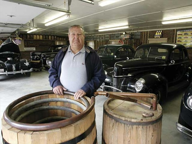 "Clay Call - ""The Uncatchable"" standing in front of an authentic Wilkes County steamer still among his fleet of 1940 Fords in his garage down in Hell's Half Acres."