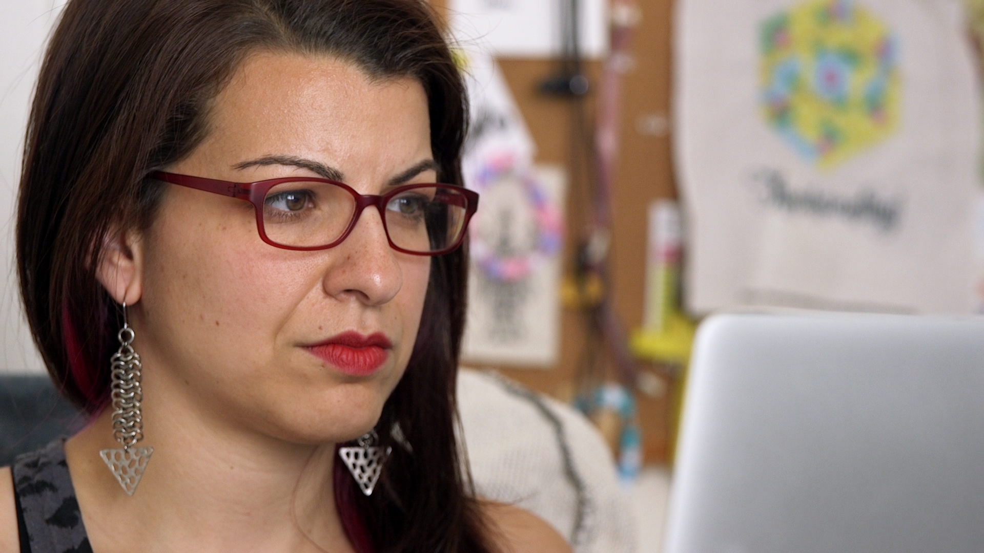 Photo of Netizens subject Anita Sarkeesian looking off camera toward a laptop screen.