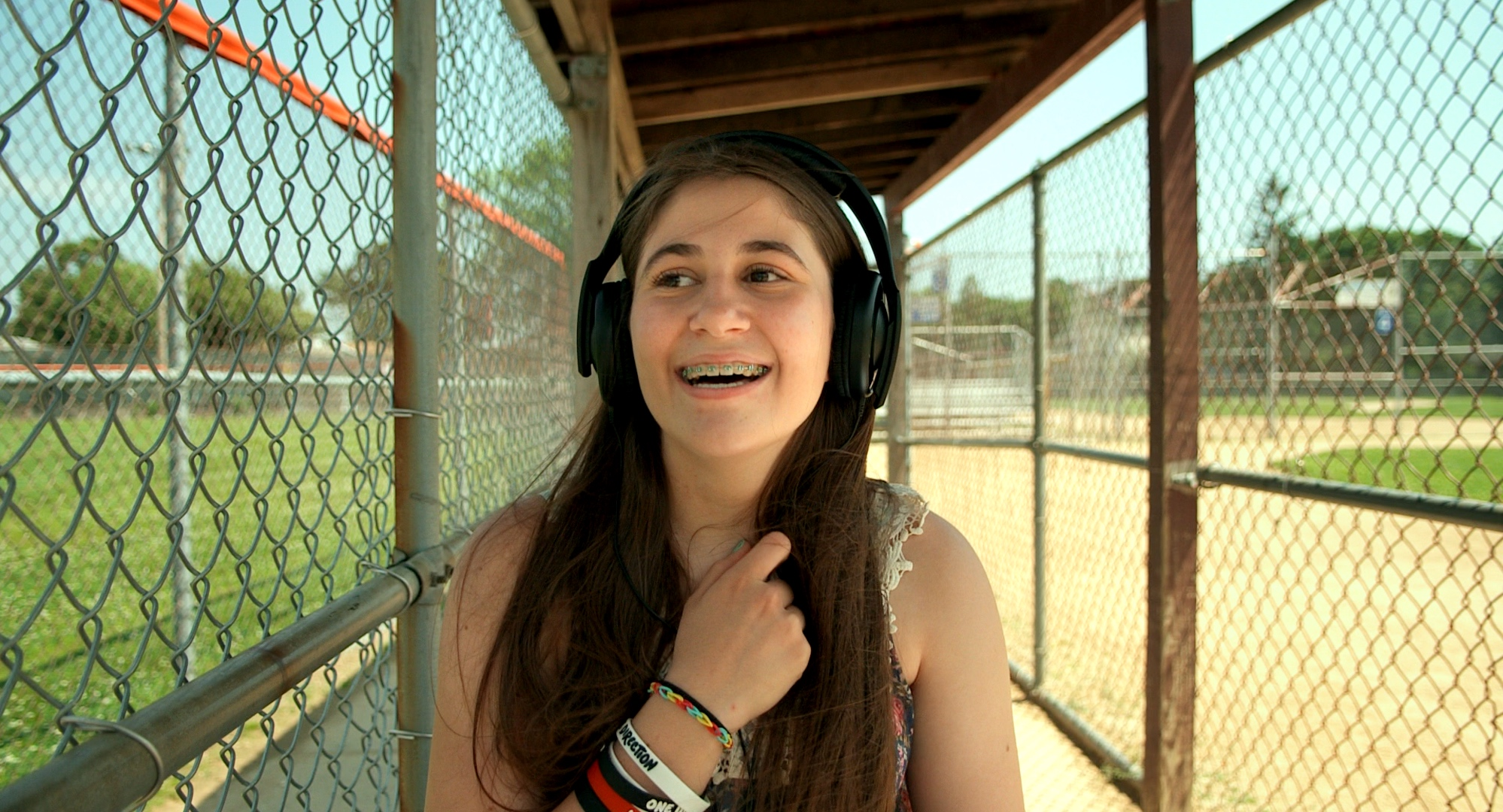 """Still from """"I Used To Be Normal"""" of a teenage girl sitting in a baseball dugout with headphones on listening to music."""