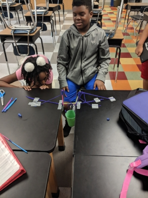 This is Korion and Tamera collaborating at Brittany Woods to build a suspension bridge using only straw, string and some tape. They were successful in holding up an entire up of sand with only two straws spanning the gap between tables.