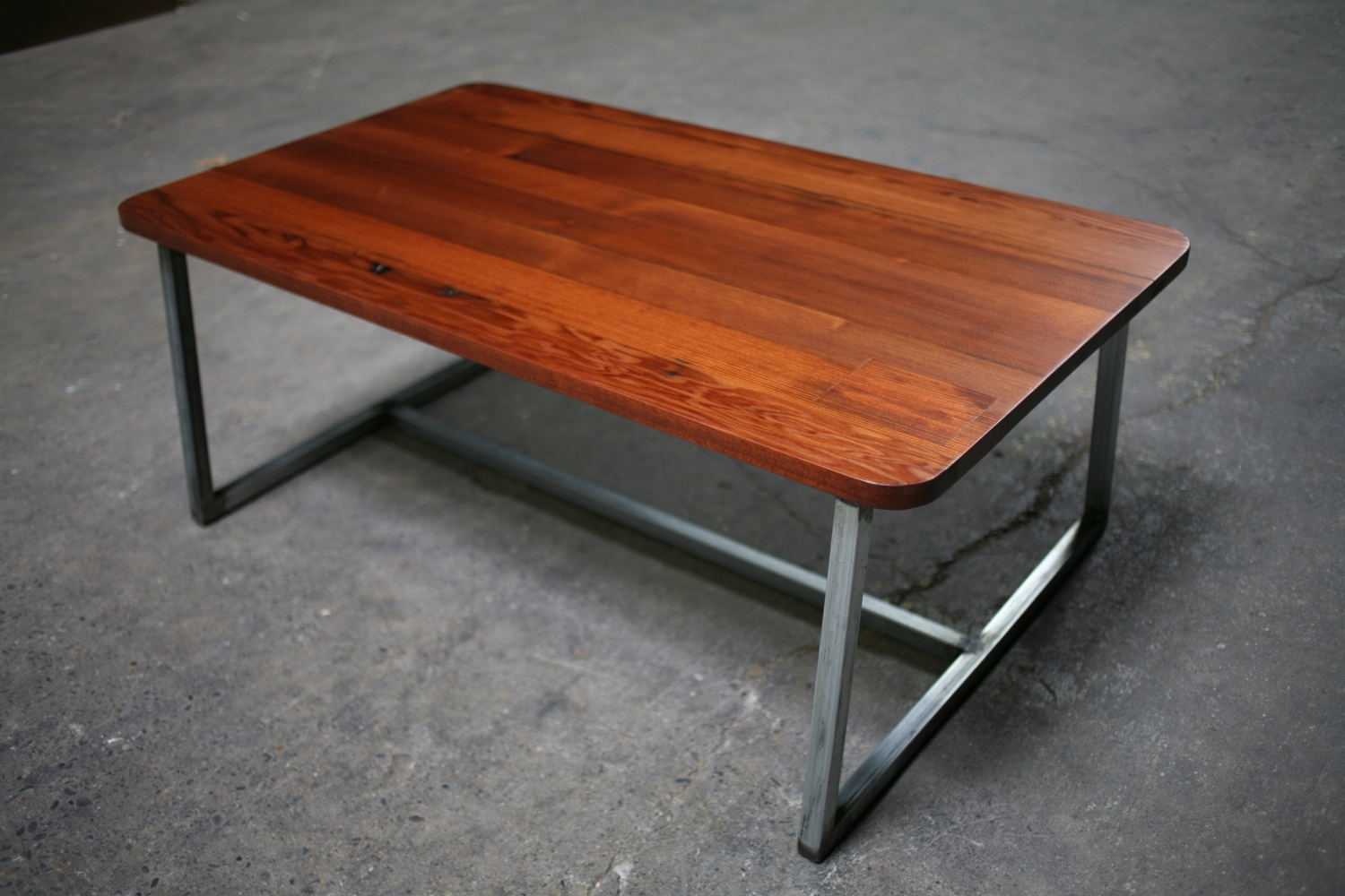 Redwood coffee table with recycled steel base.