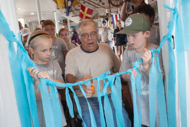 Bob Jester cuts the ribbon at the opening ceremony for Captain Bob's Quarterdeck. Photo: Katharine Schroeder