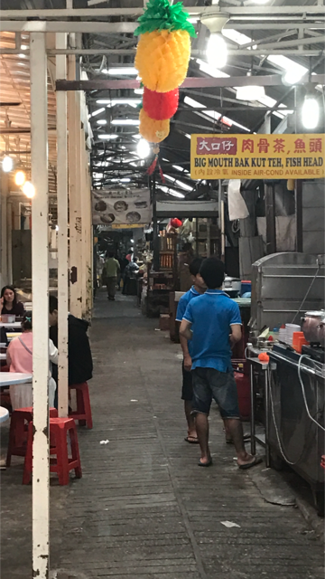 A covered alley lined with different street food stalls. The stall in the forefront offers both bak kut teh and fish head soup.