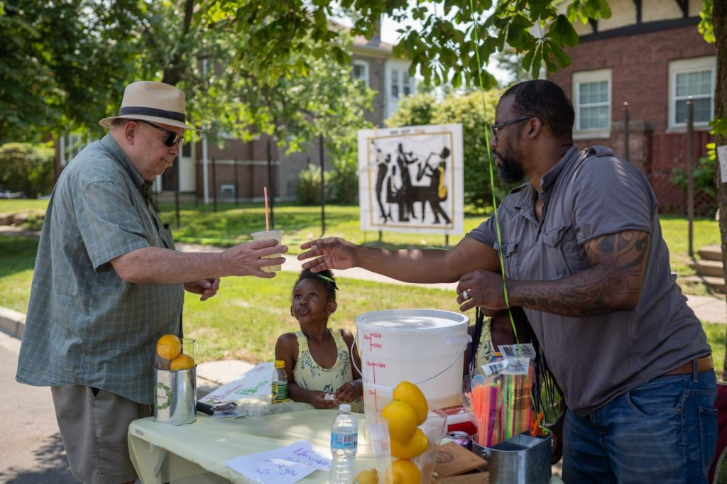 Marcus Hammonds and his daughter, Memphis, serve lemonade to a customer. Local vendors from the neighborhood were at the Back Alley Jazz Festival.