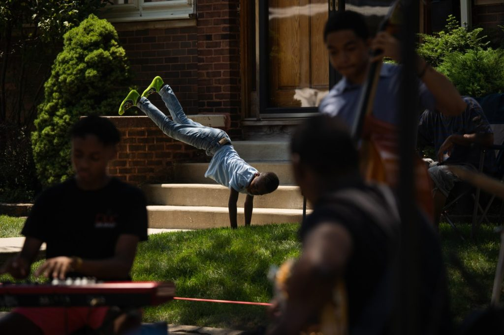 A kid does cartwheels while a band plays in the middle of the street, which was closed to vehicles during Back Alley Jazz Fest.