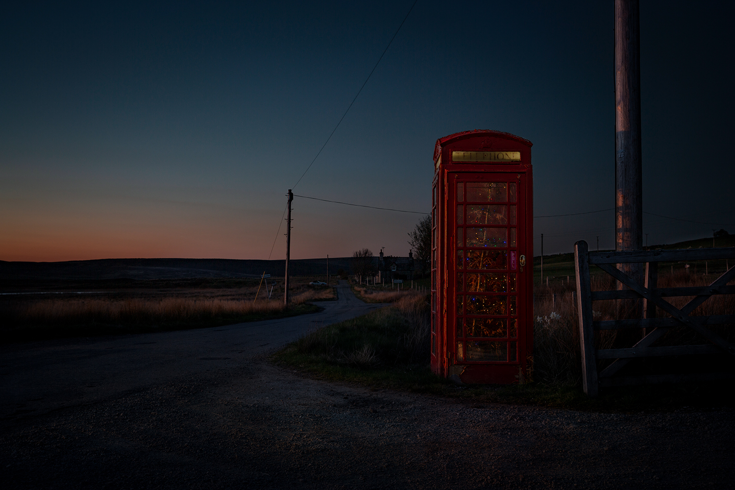 Red BT phone box with Christmas lights . Sutherland, Scotland.