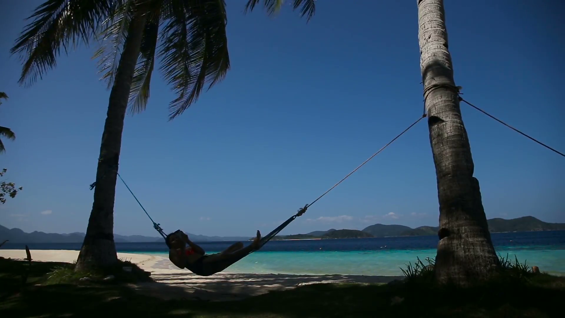 silhouette-of-man-in-hammock-on-the-beachidyllic-beach-with-coconut-trees-and-hammocktravel-concept_eimbsrb9g__F0000.png