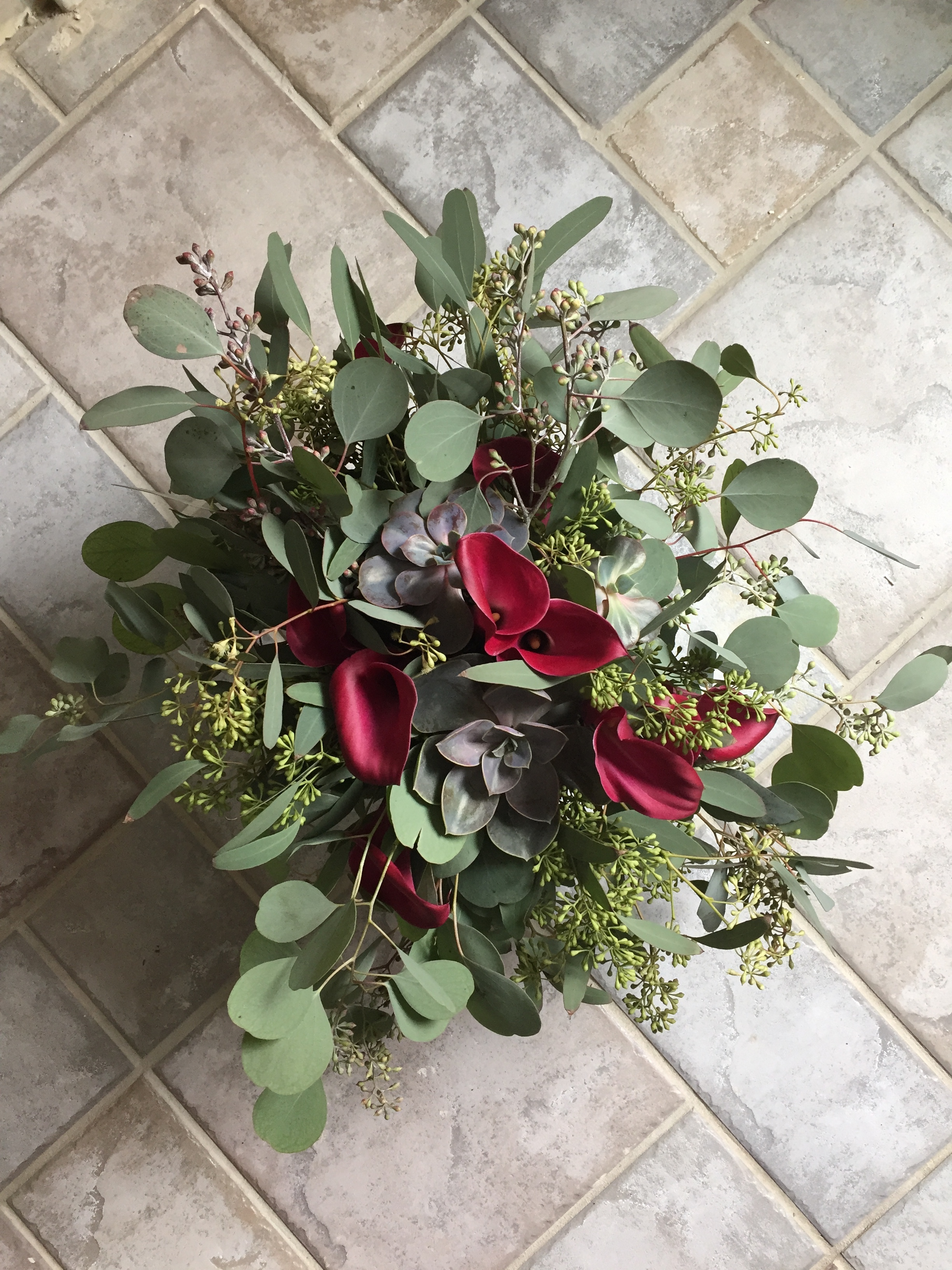 Succulents and Calla Lilies tucked into loads of eucalyptus for the bride.