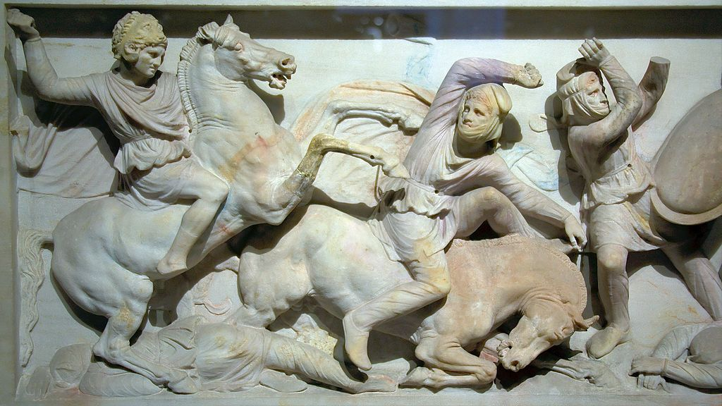 A portion of the Alexander Sarcophagus (late 4th century BCE) shows Alexander wearing a lion head helmet at the Battle of Issus.