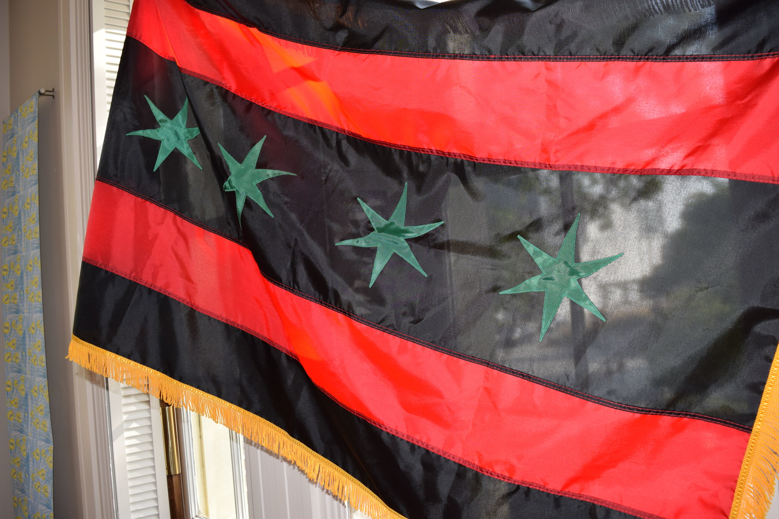 360 Nation  reimagines the Chicago state flag in red, black and green with gold fringe, the colors of the organization.