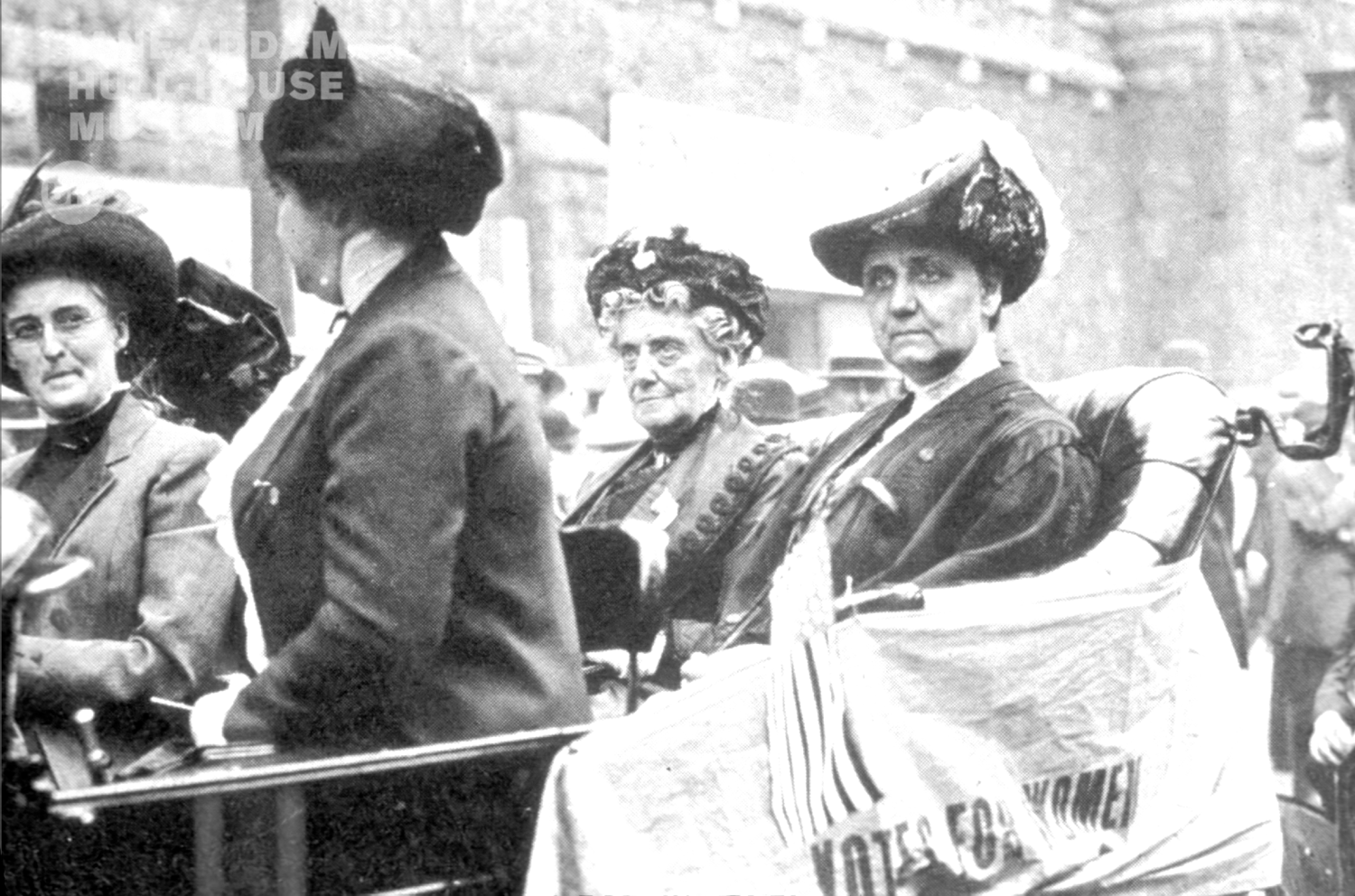"Jane Addams, seated in back on the left of the image, demonstrates with REPUBLICAN convention delegates during the 1912 Republican Party convention in chicago. The banner on the car reads, ""VOtes for women"""