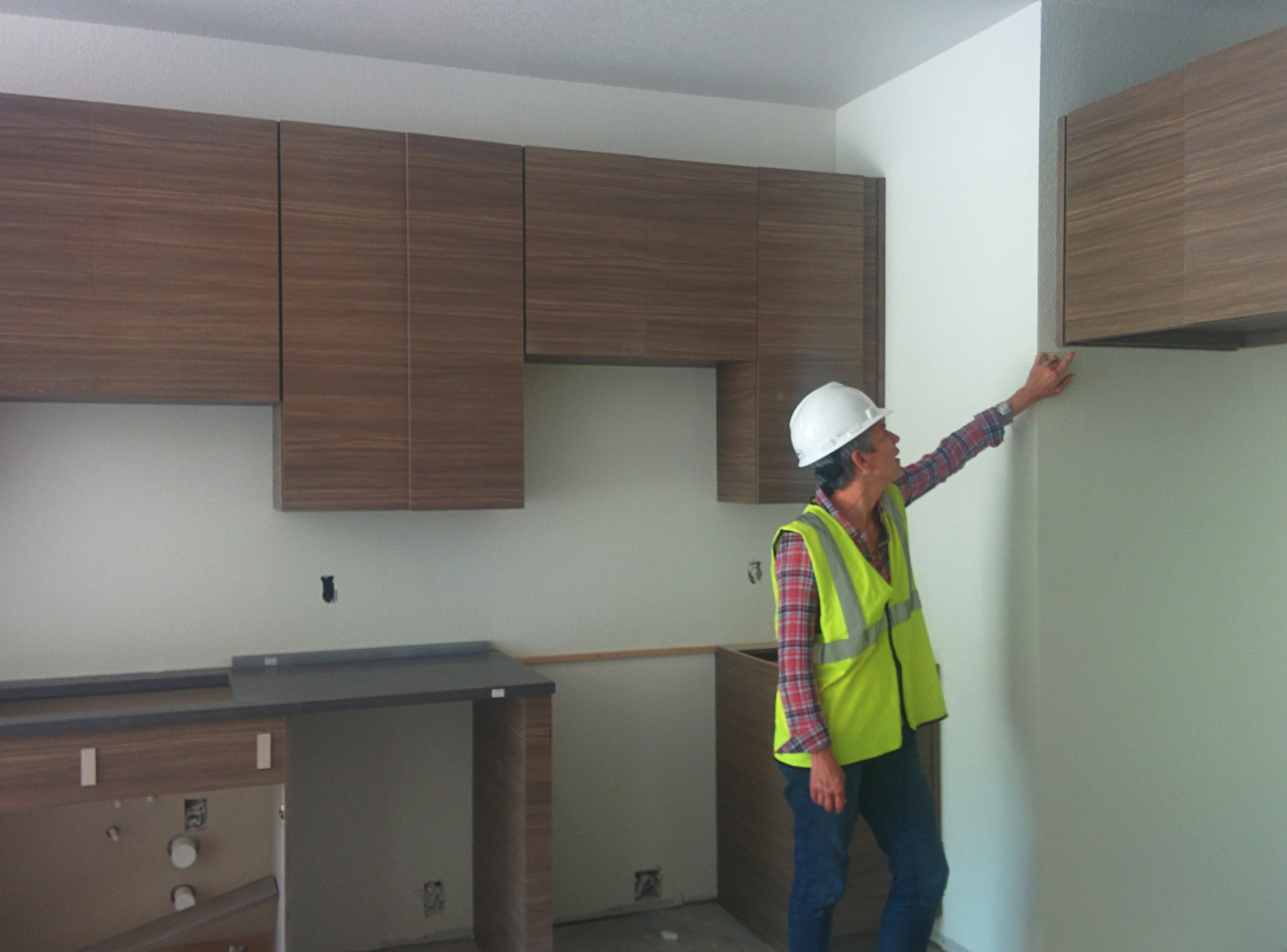 Kathy inspecting cabinetry at Unit.jpg
