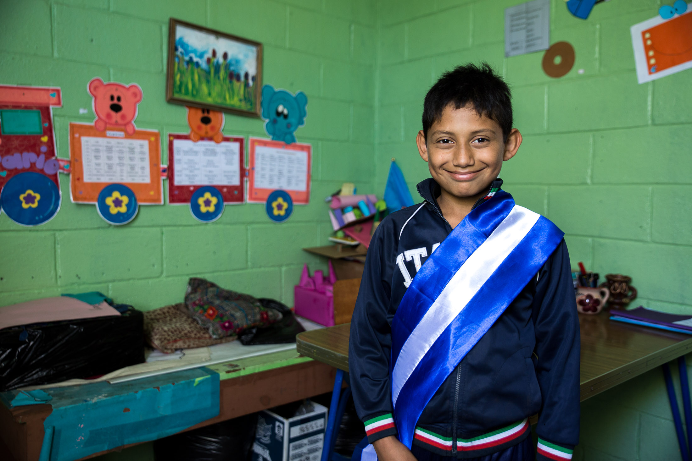 The sash signifies that David is the top student at Amigos de Jesus school