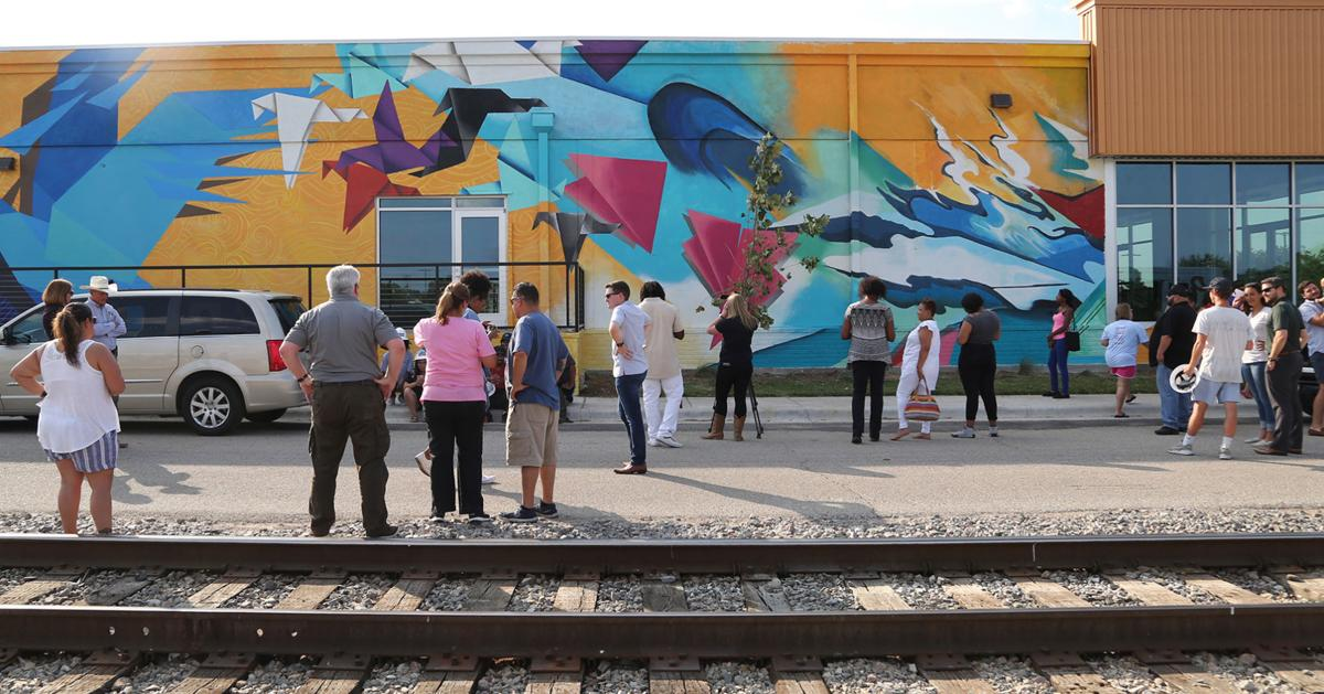 "Left: Join us for the official Mural Wrap Party and enjoy food, music, and origami! Above: Family and friends of ArtPrenticeship artists and students got a first look at ""1,000 Hopes for Waco"" after its completion earlier this month.  Photo property of Waco Tribune-Herald."