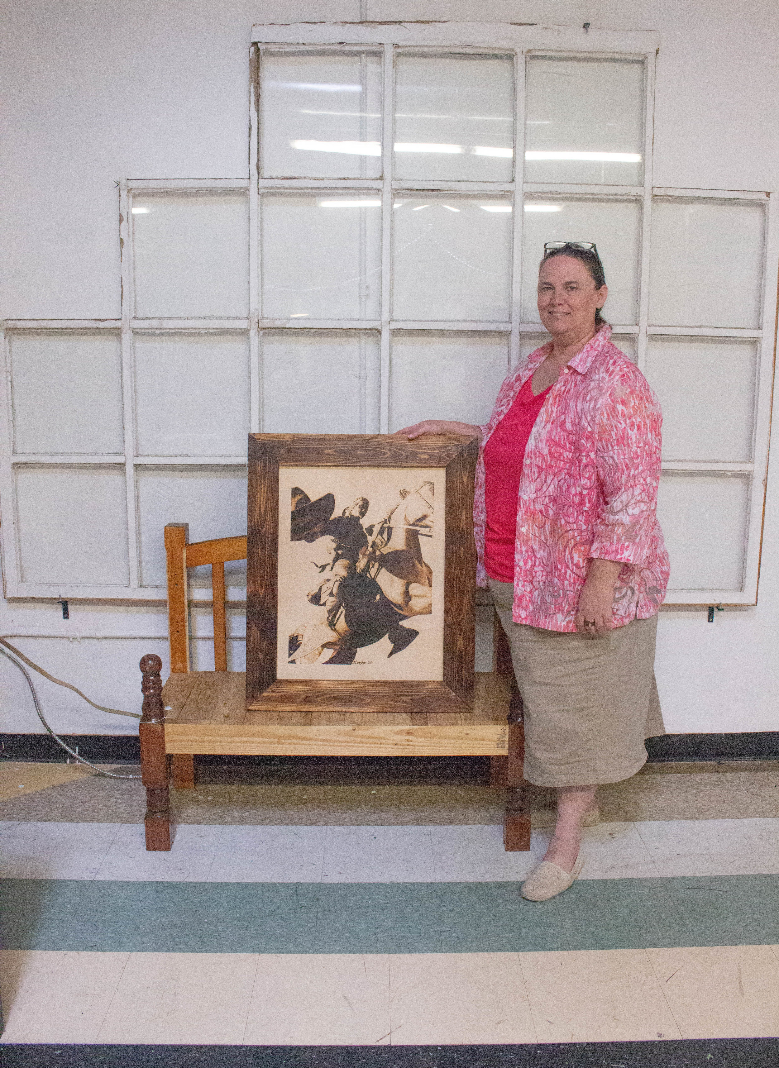 Wood Burner Marsha Wilson stands with her pyrograph  Los Vaquero.  Photo by Bradi Zapata