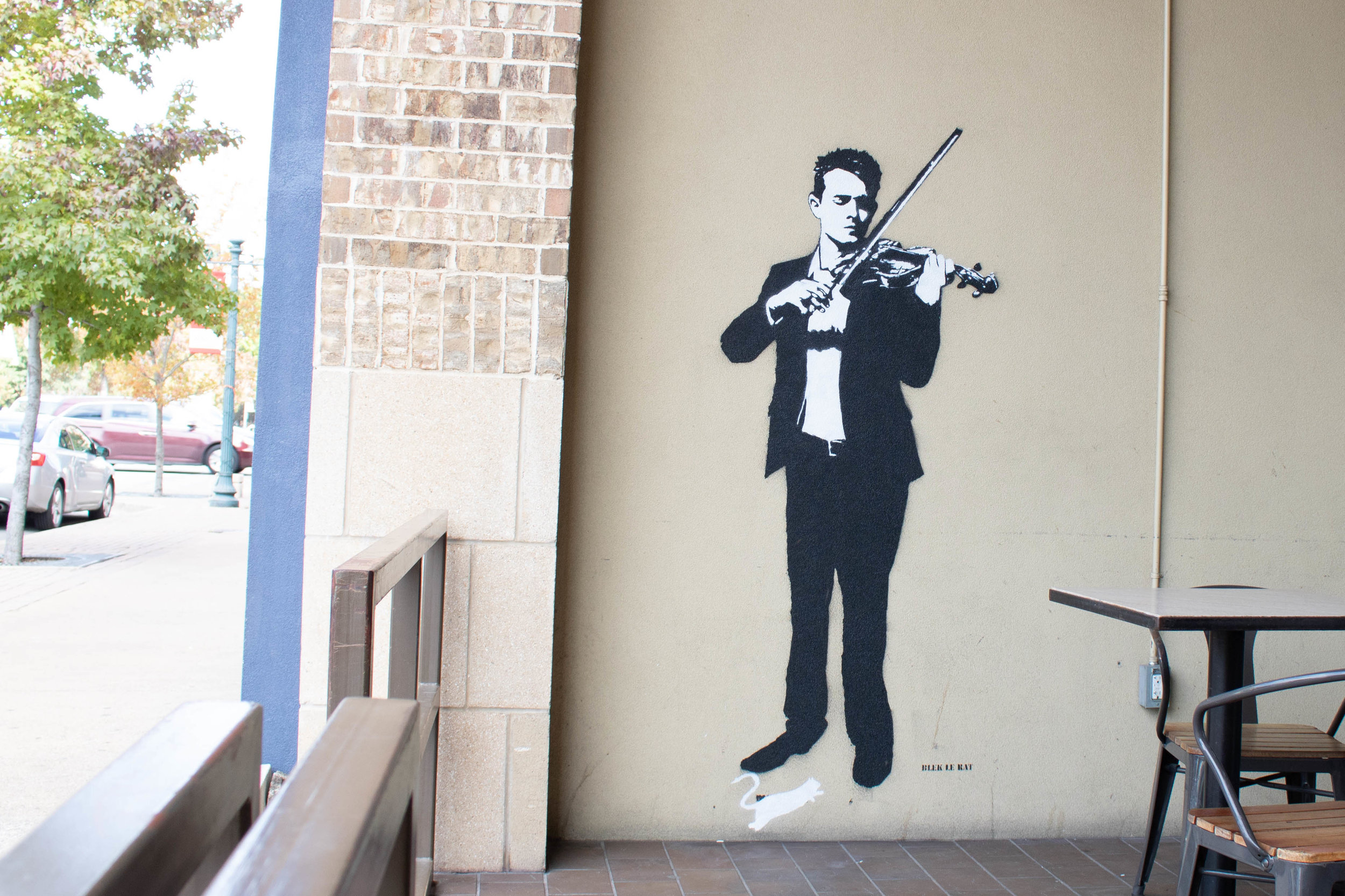 Blek le Rat's Violinist stands tall outside of Dichotomy Coffee & Spirits at 508 Austin Avenue.