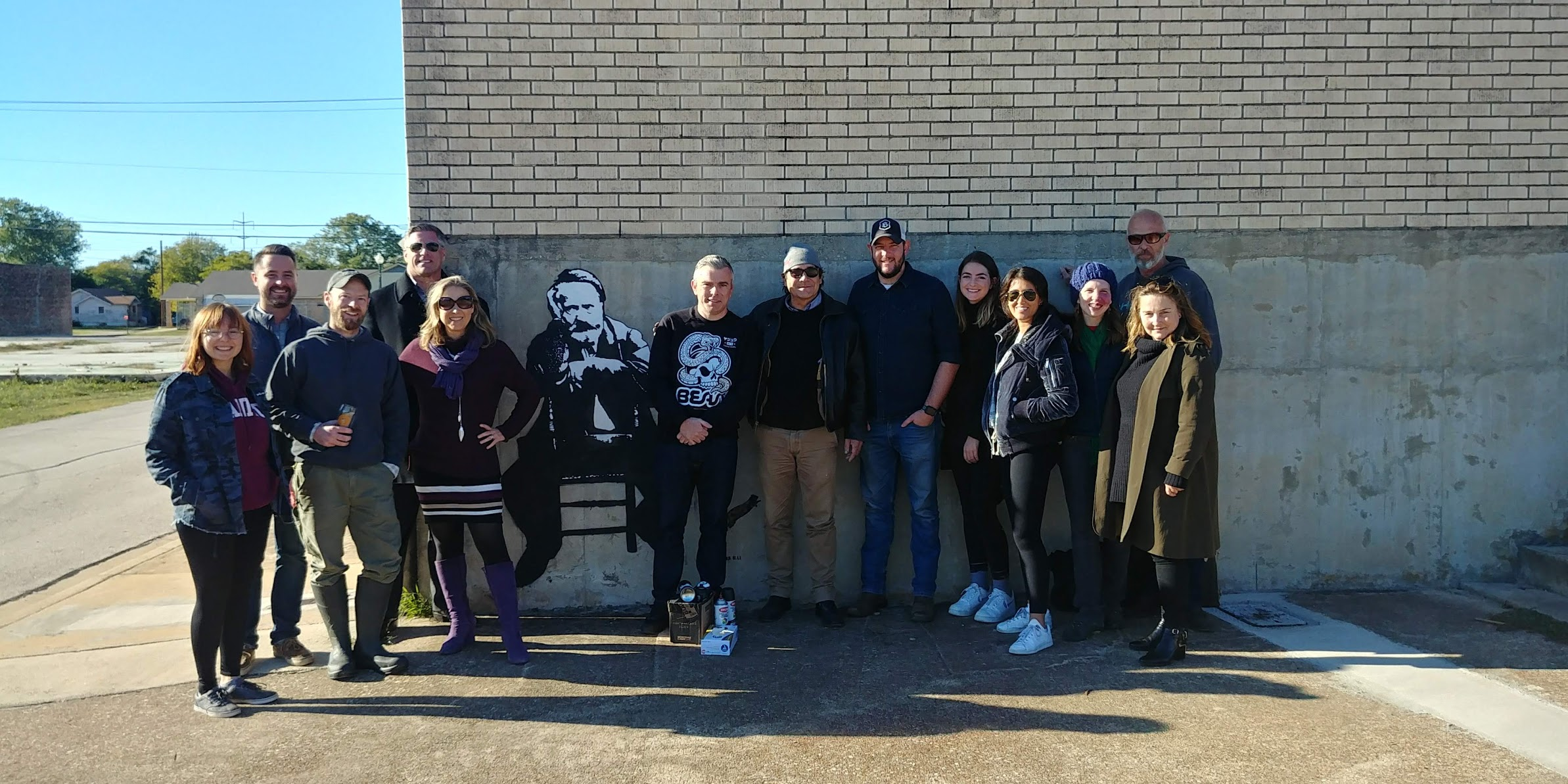 Blek le Rat and supporters stand next to one of his street art piece's in Waco, Texas