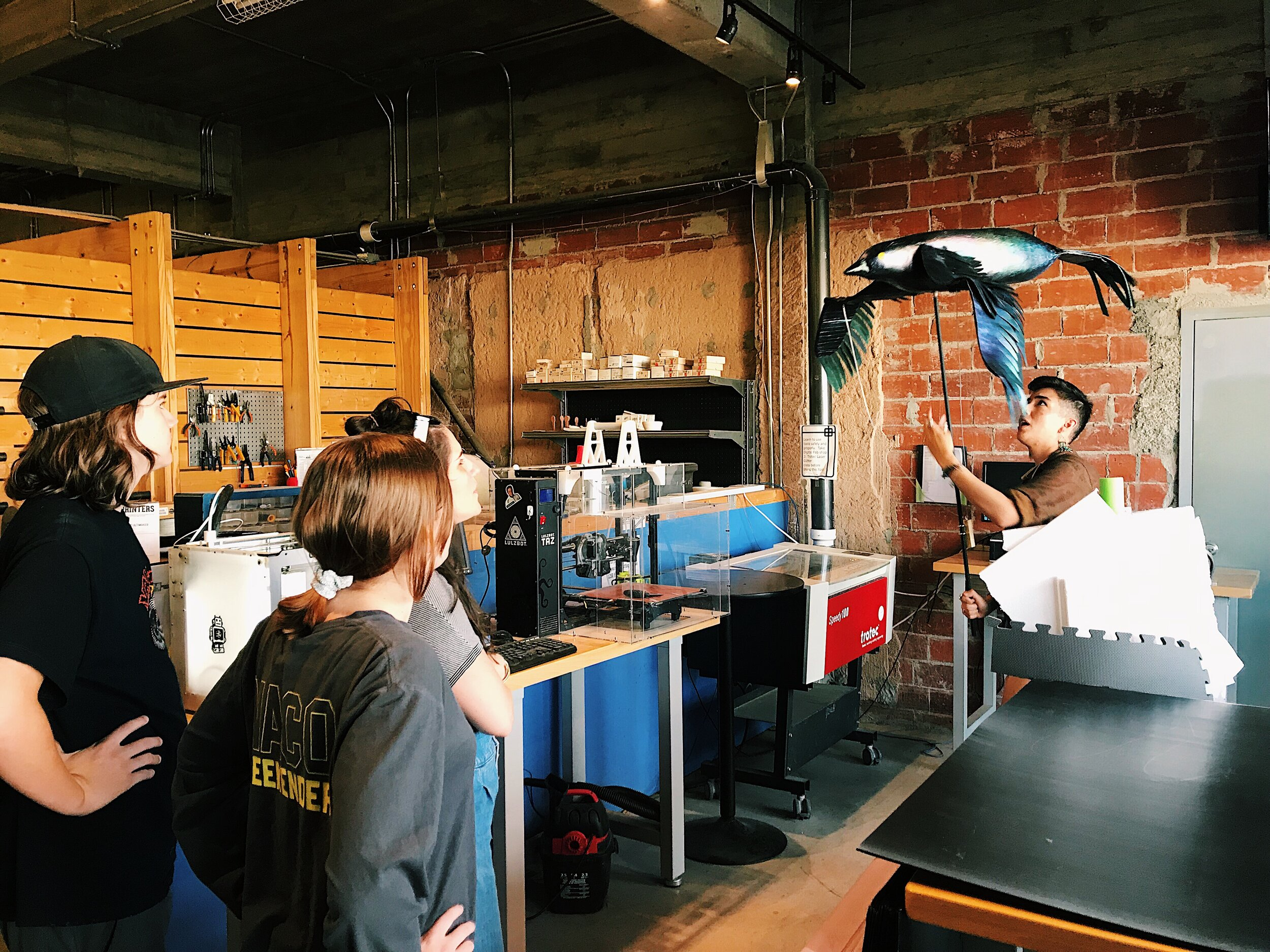 """Local puppet artist, PJ Kelly, demonstrates how the giant grackle parade puppets operate during the """"Great Grackles! – giant puppet parade workshop"""" at Maker's Edge."""