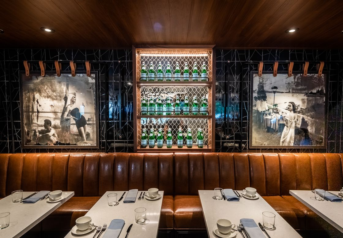 Italy's go-to table water San Pellegrino doubles as glowing green wall decor, alongside retro images of women posing along scenic shores.