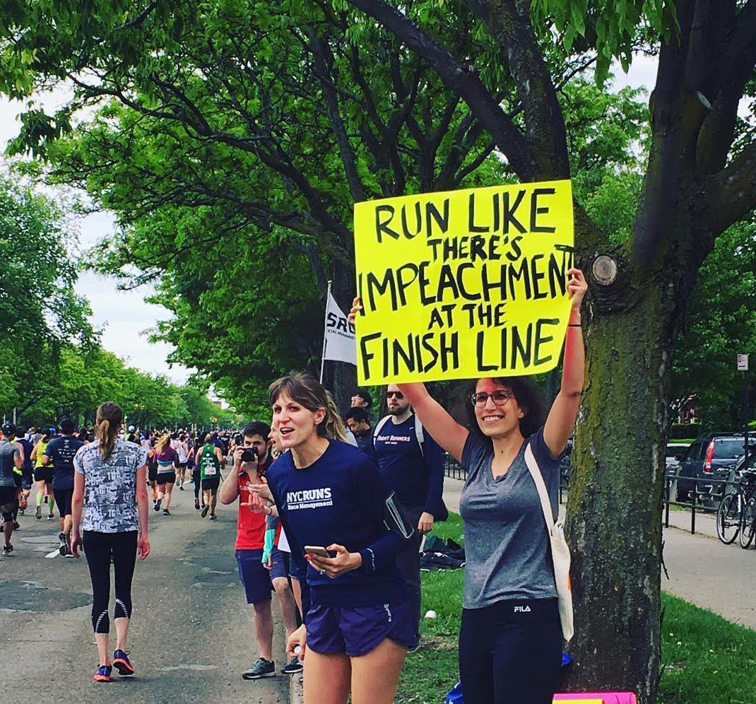 Kara (holding the sign)near the end of this year's Brooklyn Half Marathon. The promise of impeachment might actually motivate us to run next year!
