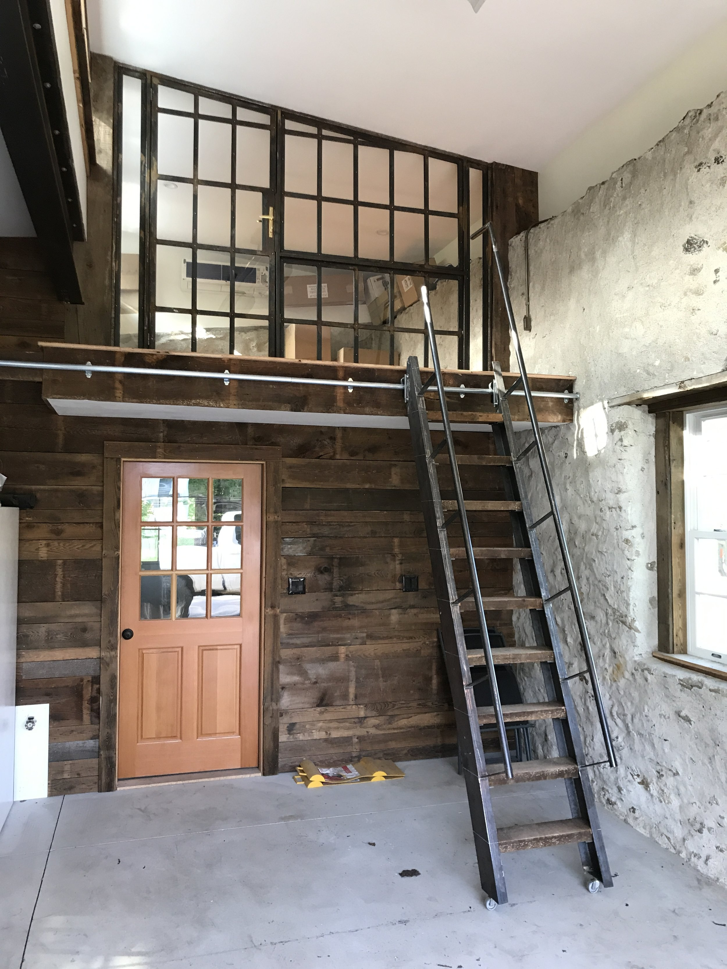 """Fabricated steel """"factory office"""" style window wall and rolling stair."""
