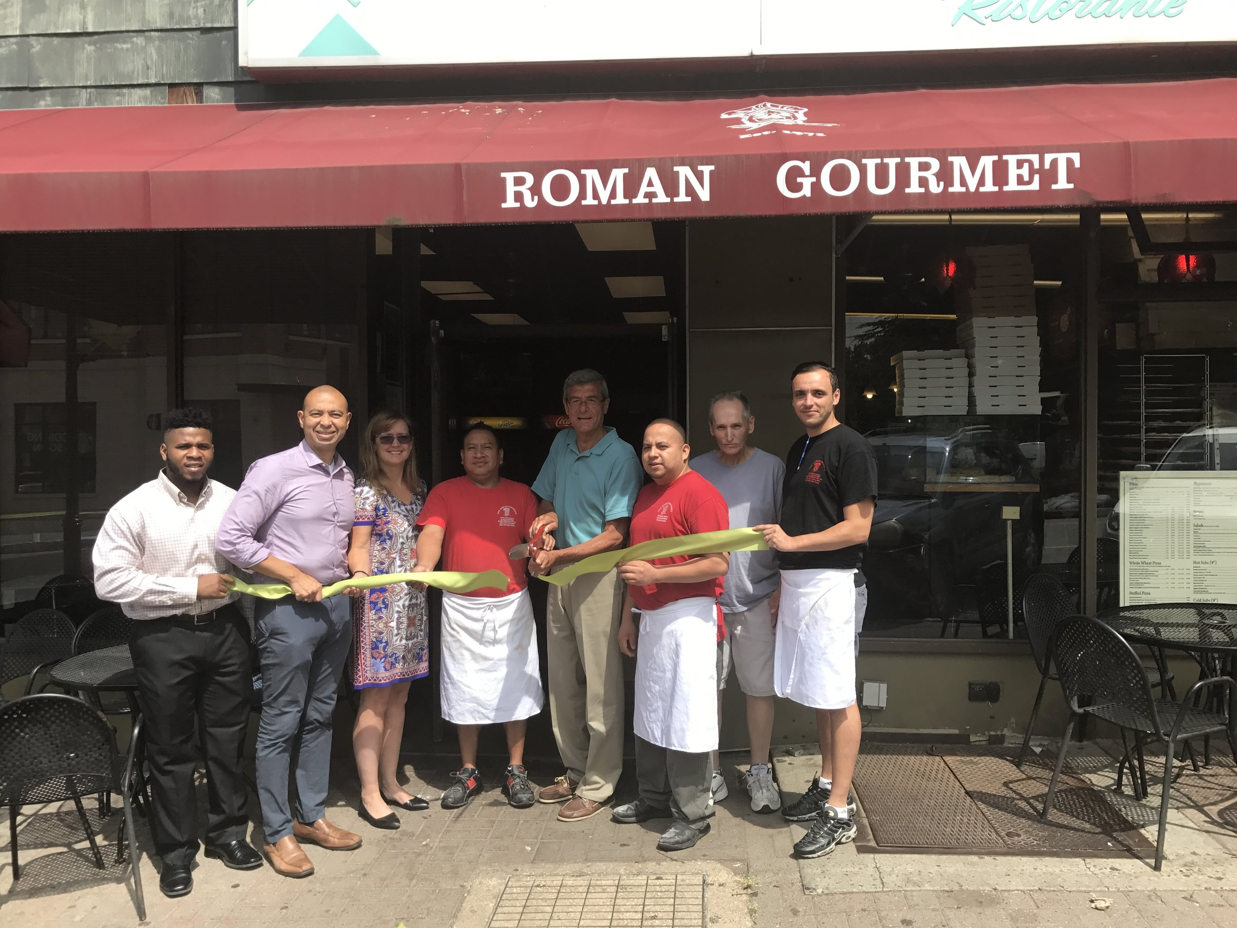 Left to right -- Uche Uneze (Maplewood Green Business intern), Township Committeeman Frank McGehee, Sheila Baker Gujral (Maplewood Environmental Advisory Committee), Johnny Calle (Roman Gourmet), Mayor Vic DeLuca, Pablo Carcamo (Roman Gourmet), John Brown (Roman Gourmet), and Lamine Ameur (Roman Gourmet)