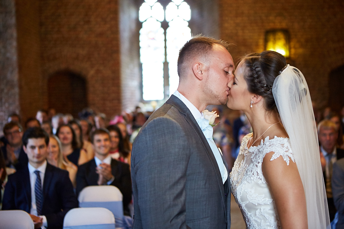 A wedding day couple kiss at Tattershall Castle Lincolnshire