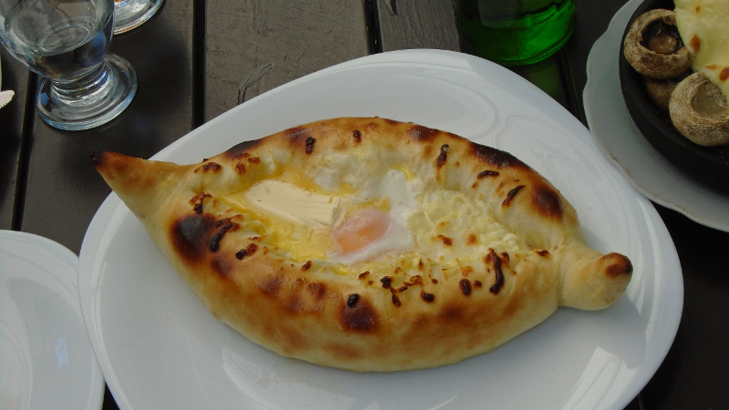 This is fancy ხათჩაპური. The dough is formed into a boat with hot cheese in the center. A raw egg and pat of butterfloats on the cheese. To eat, you tear off pieces of bread and stir them in the center, mixing it all. You generally only see this in restaurants.